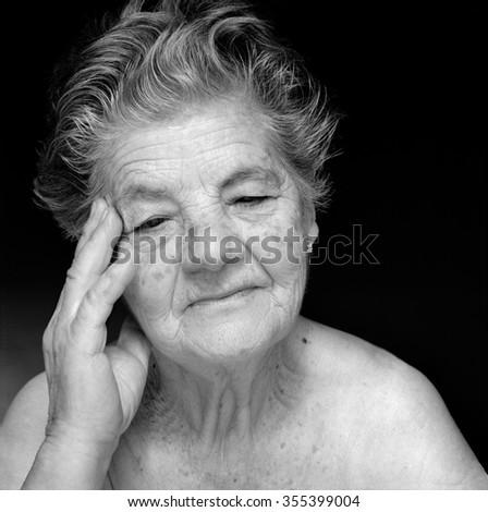 Medium format film photography shot.Black and white portrait detail of melancholic senior woman against black background - stock photo