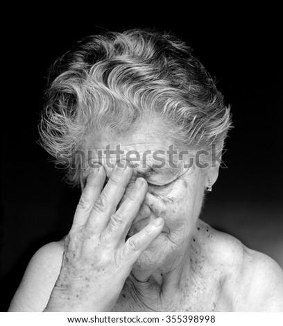 Medium format film photography shot. Black and white portrait of anguished elderly woman against black background. - stock photo