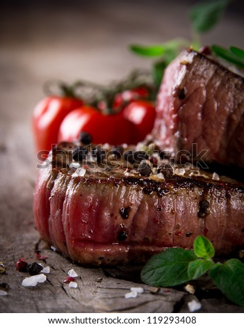 Medium Grilled bbq steaks over wooden background - stock photo