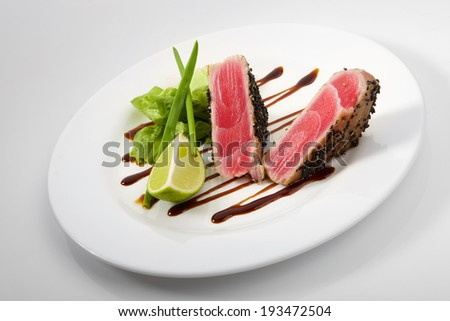 Medium grilled tuna steak with vegetables isolated on white background