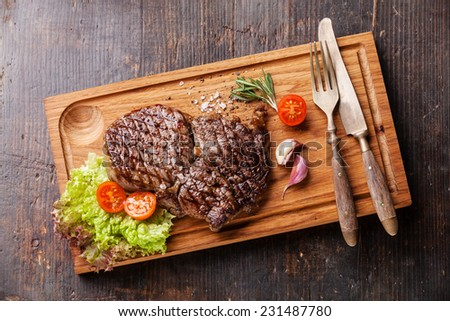 Medium rare grilled Beef steak Ribeye on cutting board on wooden background - stock photo