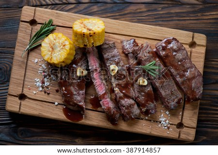 Medium rare grilled rancho steak on a wooden serving board, top view