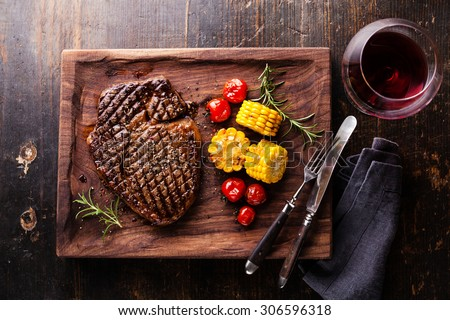 Medium rare grilled Steak Ribeye Black Angus with corn and cherry tomatoes on serving board block on wooden background - stock photo