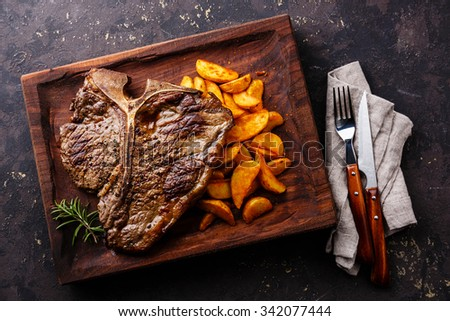 Medium rare Grilled T-Bone Steak with potato wedges on serving board block on dark background - stock photo
