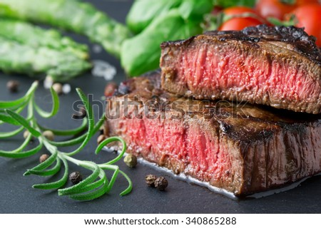 medium roasted steak with asparagus and tomatoes on slate plate - stock photo