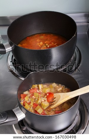 Medium saucepan of Boiling okra and tomato mixture in foreground to be added to larger sauce pan with the Creole style Chicken Gumbo. - stock photo