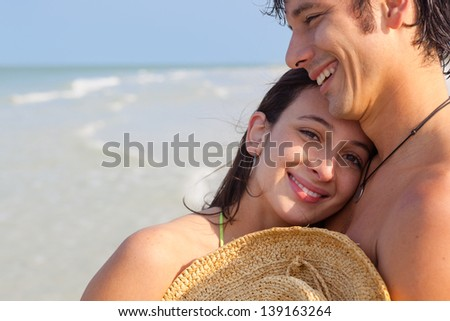 Medium shot of Latin young woman being embraced by man on Florida Beach