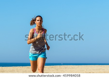 Medium shot of young woman jogging outdoors against blue sky.