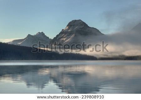 Medium shot sunrise lights over Bow Lake on a foggy morning. Taken at Banff National Park, Alberta, Canada - stock photo