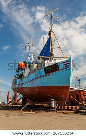 Medium-sized fishing boat standing in a drydock for repairs.