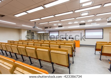 Medium-sized lecture hall with screens and whiteboard