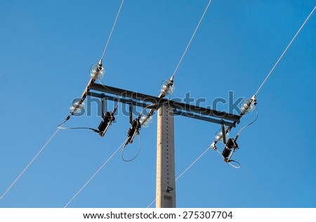 Medium voltage metal tower with green glass insulators backlit on blue sky - stock photo