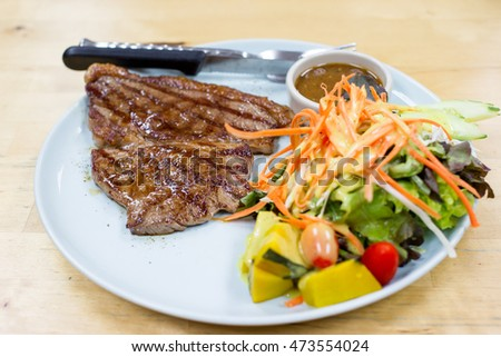 Medium well beef steak with salad close up.