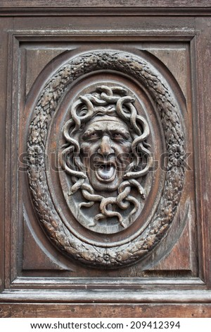 Medusa head carving on a wooden door - stock photo