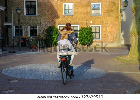 Meerkerk, municipality Zederik, Netherlands - April 13, 2015: The woman and little girl riding a bicycle in the Dutch city Meerkerk, Netherlands