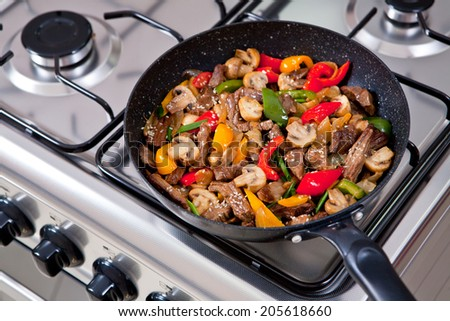 meet and vegetables being cooked on a gas stove - stock photo