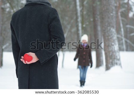 Meet guy and girl in winter park. Decorative heart in his hand Man behind. Pleasant surprise - stock photo