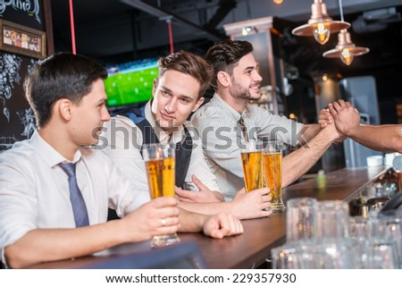Meet real friends. Four friends men drinking beer and having fun together in the bar and look at the camera