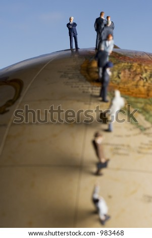 Meet the boss, business figures in a line on a globe - stock photo