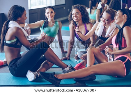 Meet up on the mat. Beautiful young women in sportswear discussing something with smile and using smartphone while sitting on exercise mat at gym