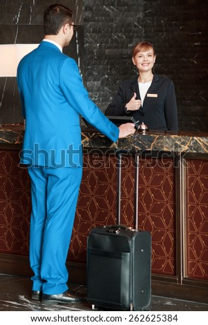 Meeting a guest. Full length selective focus view of the charming female receptionist showing her thumb up and meeting a guest businessman in blue suit with the suitcase below  - stock photo