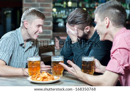 Meeting at the pub. Three happy friends drinking beer at the pub - stock photo