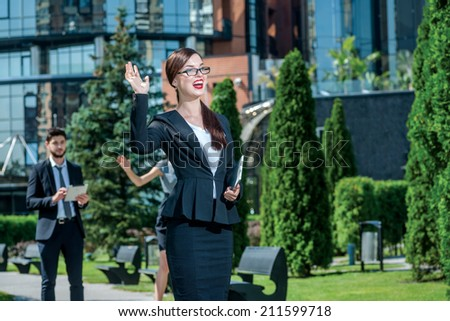 Meeting business clients. Business woman in glasses holding a tablet in his hands and greets the customer while two businessmen decide things standing in the background - stock photo