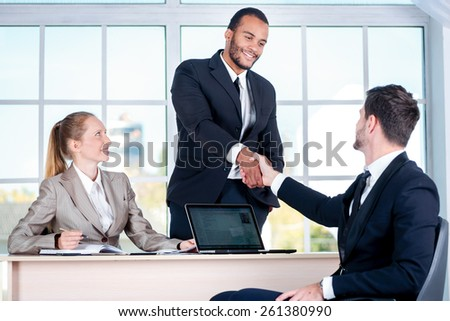 Meeting business partners. Three businessman sitting at the table while three businessmen looking at the camera and smiling while standing in office shaking hands with each other - stock photo