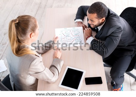 Meeting colleagues. Two businessman sitting at the table and view the documents. Businessmen examine the data and graphics. - stock photo