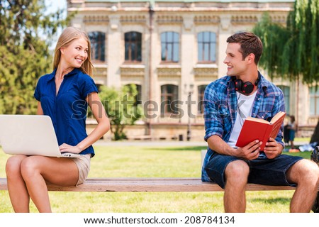 Meeting each other at the first time. Handsome young man sitting on the bench and reading book while beautiful woman sitting near him and using computer - stock photo