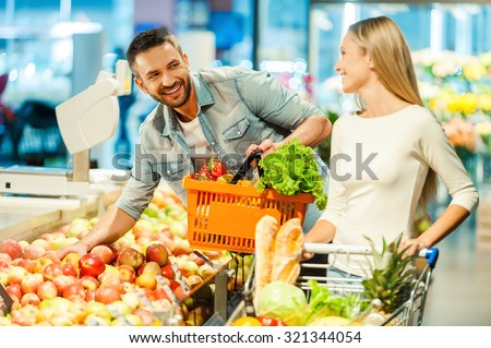 Meeting in supermarket. Beautiful young couple choosing products in supermarket and looking at each other with smile - stock photo