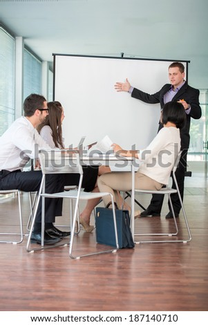Meeting of business people in modern office listening presentation - stock photo