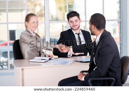 Meeting of Chiefs. Three successful business people sitting in the office and do business while businessmen shake hands with each other and work at a laptop - stock photo