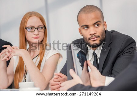 Meeting of four confident people. Four confident successful businessmen at a meeting while sitting at a table discussing business case in the office showing thumbs up - stock photo