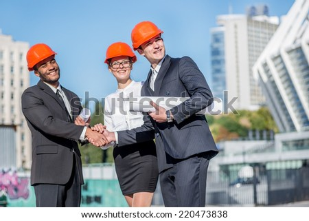 Meeting of the group of architects. Three confident business architect in protective helmet standing on the site and keep the blueprints in hand while shaking hands