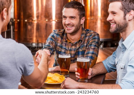 Meeting old friends. Three happy young men sitting in beer pub together while two of them handshaking - stock photo
