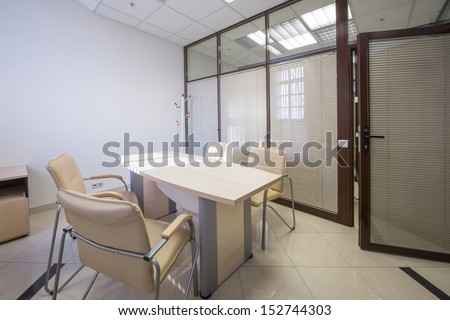 Meeting room blinds closed with a table and leather chairs