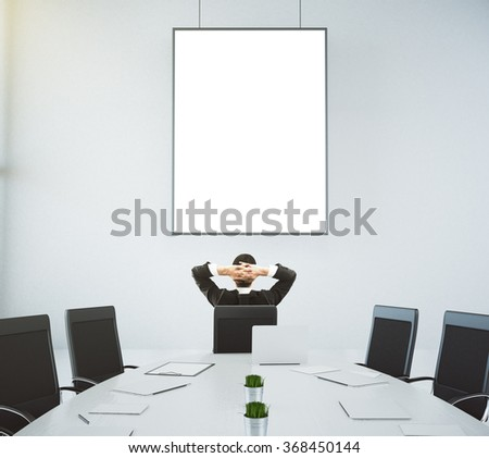 Meeting room with a table and a businessman sitting in a chair and looking at the wall with blank picture frame, mock up 3D Render - stock photo