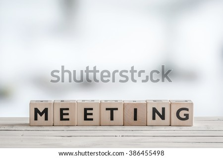 Meeting sign with wooden blocks on an office desk - stock photo