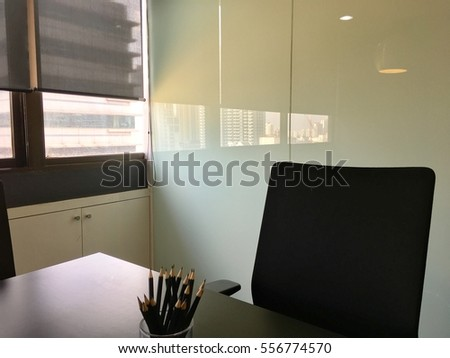 meeting table and chair office with glass whiteboard window and high building in background