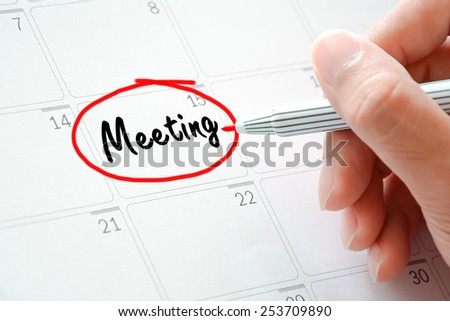 Meeting text on the calendar (or desk planner) circled with red marker - stock photo