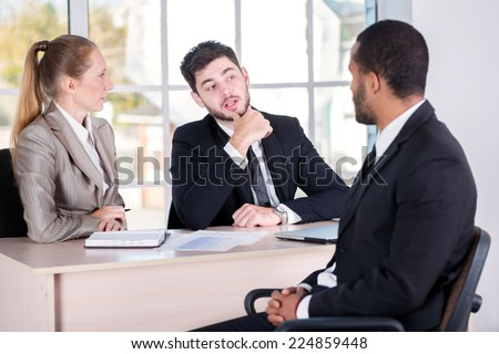 Meeting with a client. Three successful business people sitting in the office and do business while businessman working at his desk