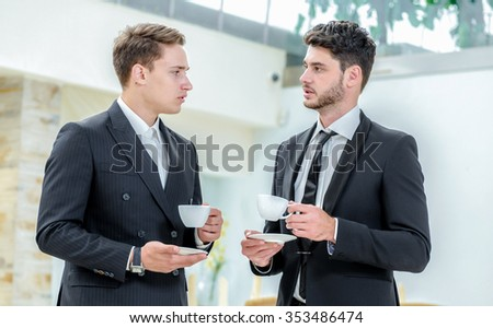 Meeting with partner. Two successful businessman standing in the restaurant and drink coffee while talking to each other. Businessman dressed in formal wear.