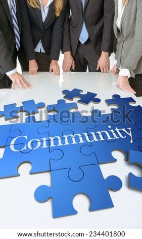 Meeting with people around a table with a puzzle with the word community - stock photo