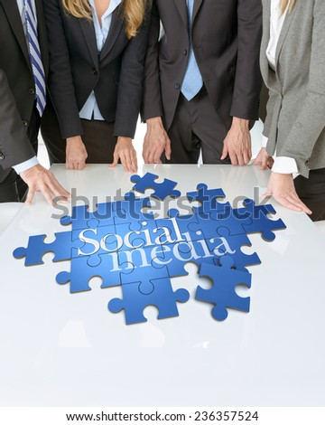 Meeting with people around a table with a puzzle with the words Social media - stock photo