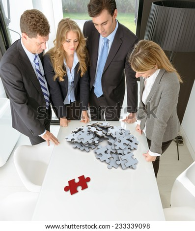 Meeting with people around a table with a white puzzle with a red piece standing apart - stock photo