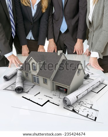Meeting with people around a table with an architectural model on top of documents and charts - stock photo