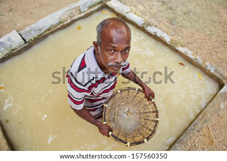 MEETIYAGODA, SRI LANKA - SEPTEMBER 9: The worker is washing the stones extracted from moonstone mine on September 9, 2013 in Meetiyagoda. Moonstone is one of gems found in Sri Lanka. - stock photo