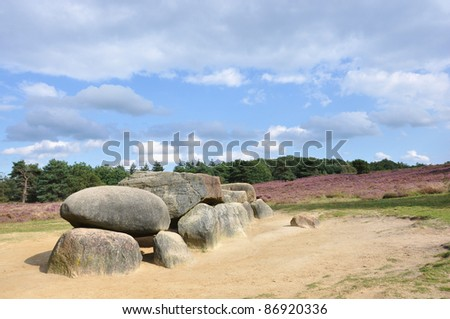 Megalith on a hill with heather and forest - stock photo