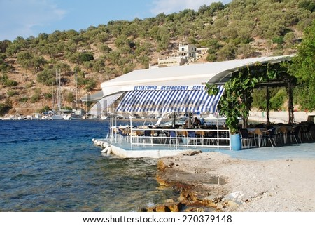 MEGANISSI, GREECE - AUGUST 31, 2008: The beach taverna at Spilia Bay on the Greek island of Meganissi. With a population of around 1100 people, the Ionian island is a satellite of nearby Lefkada. - stock photo